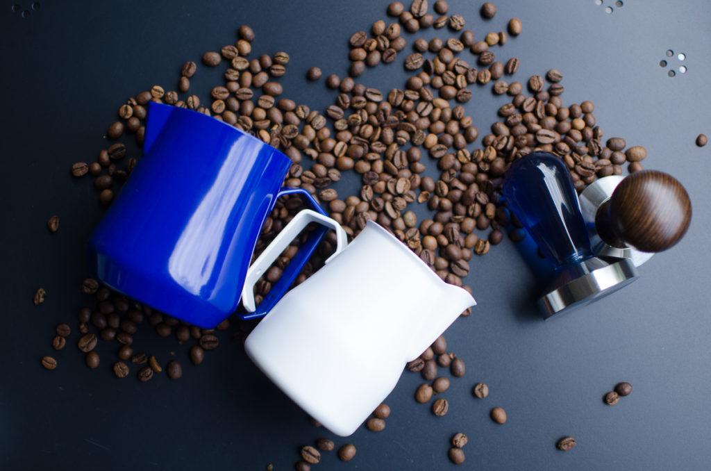 biały i niebieski dzbanek do mleka ziarna kawy na stole