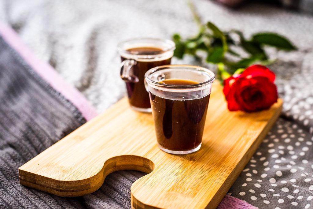 dwa kubki kawy na drewnianej desce