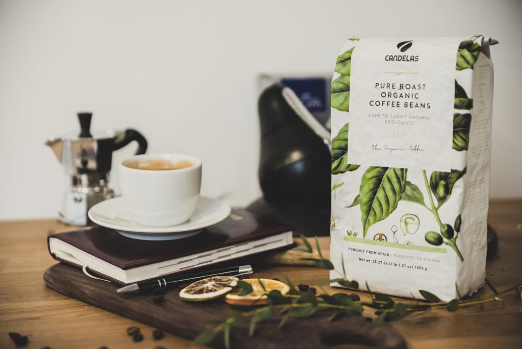 kawa organiczna w białym opakowaniu obok białej filżanki