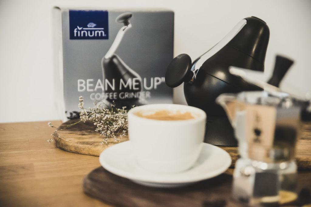młynek ręczny obok filiżanka kawy