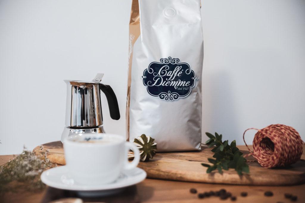 kawa w białym opakowaniu obok białej filiżanki
