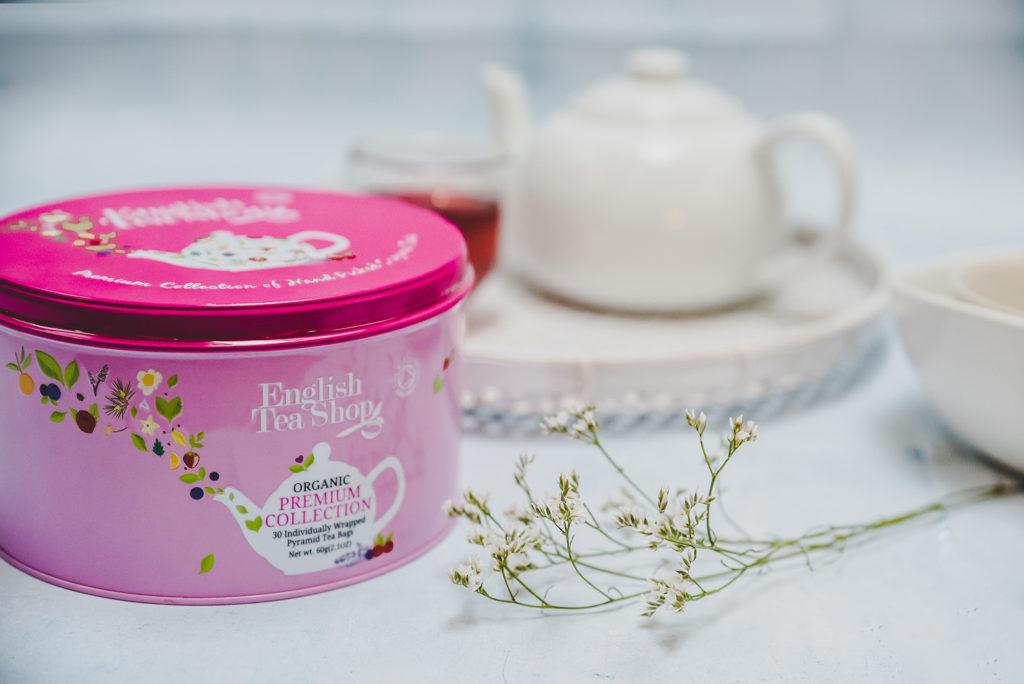 różowa puszka herbaty, a w tle zastawa do herbaty