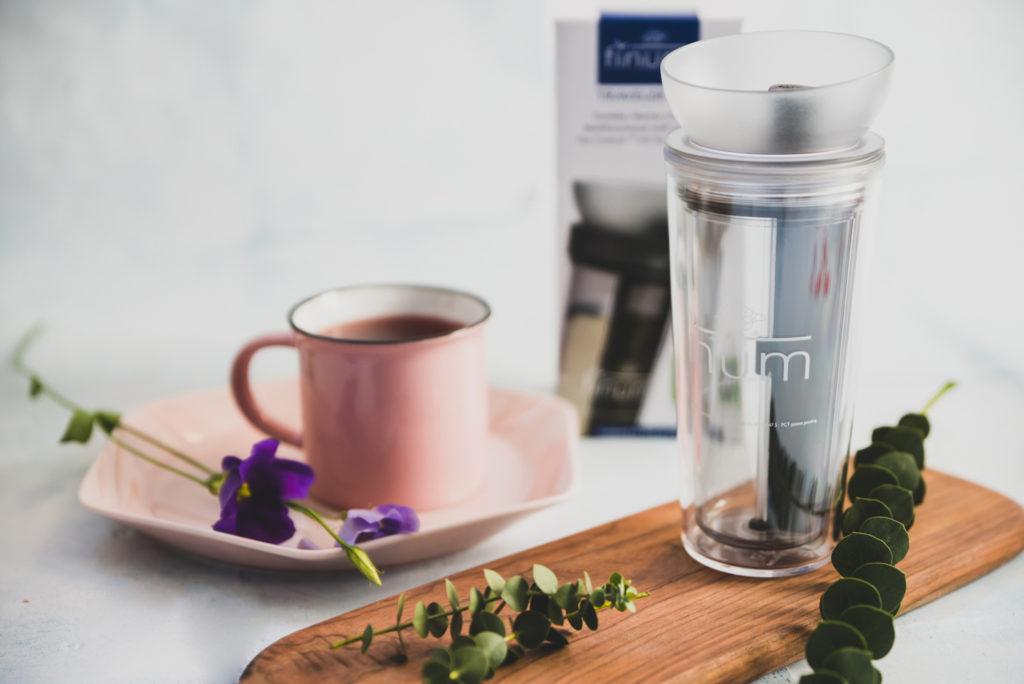 szklany zaparzacz do kawy na drewnianej desce różowy kubek z kawą