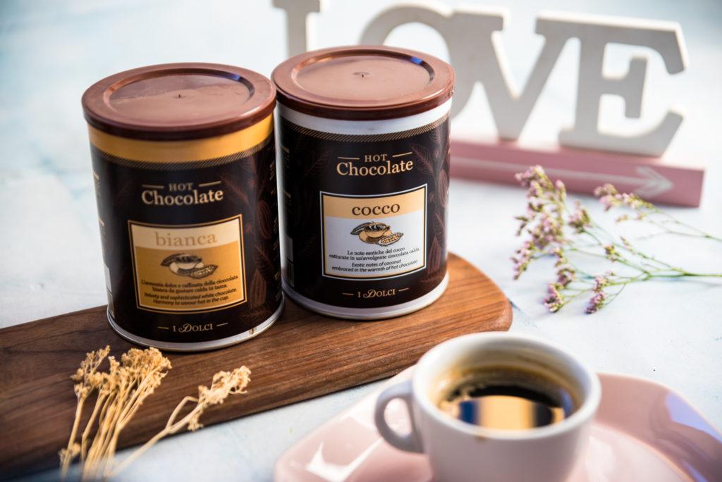 dwie puszki gorącej czekolady na drewnianej desce