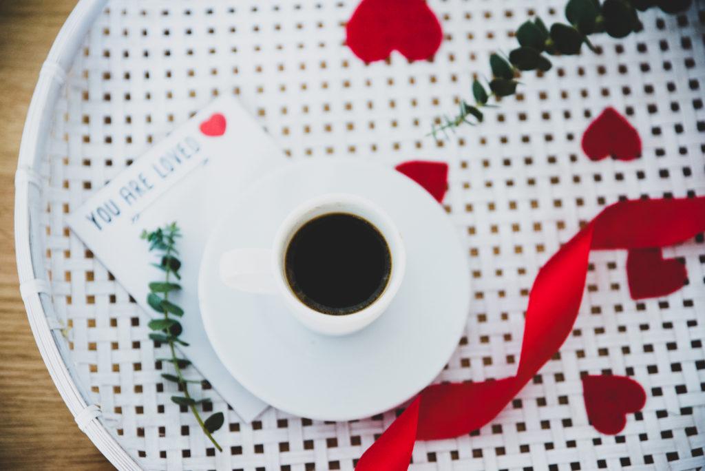 biała filiżanka z kawą i czerwoną wstążką